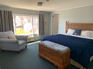 This spacious bed room features a king bed with beautiful blue accents looking out to the south towards Anclam Park.